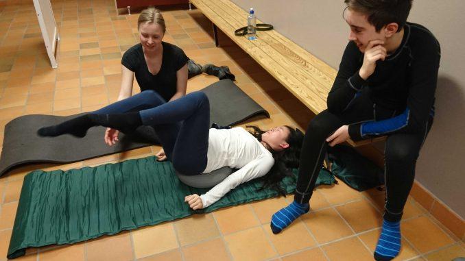 Linn Bartilson tränar bålstabilitet, Emy Nyberg och Gustav Eneberg hjälper till.