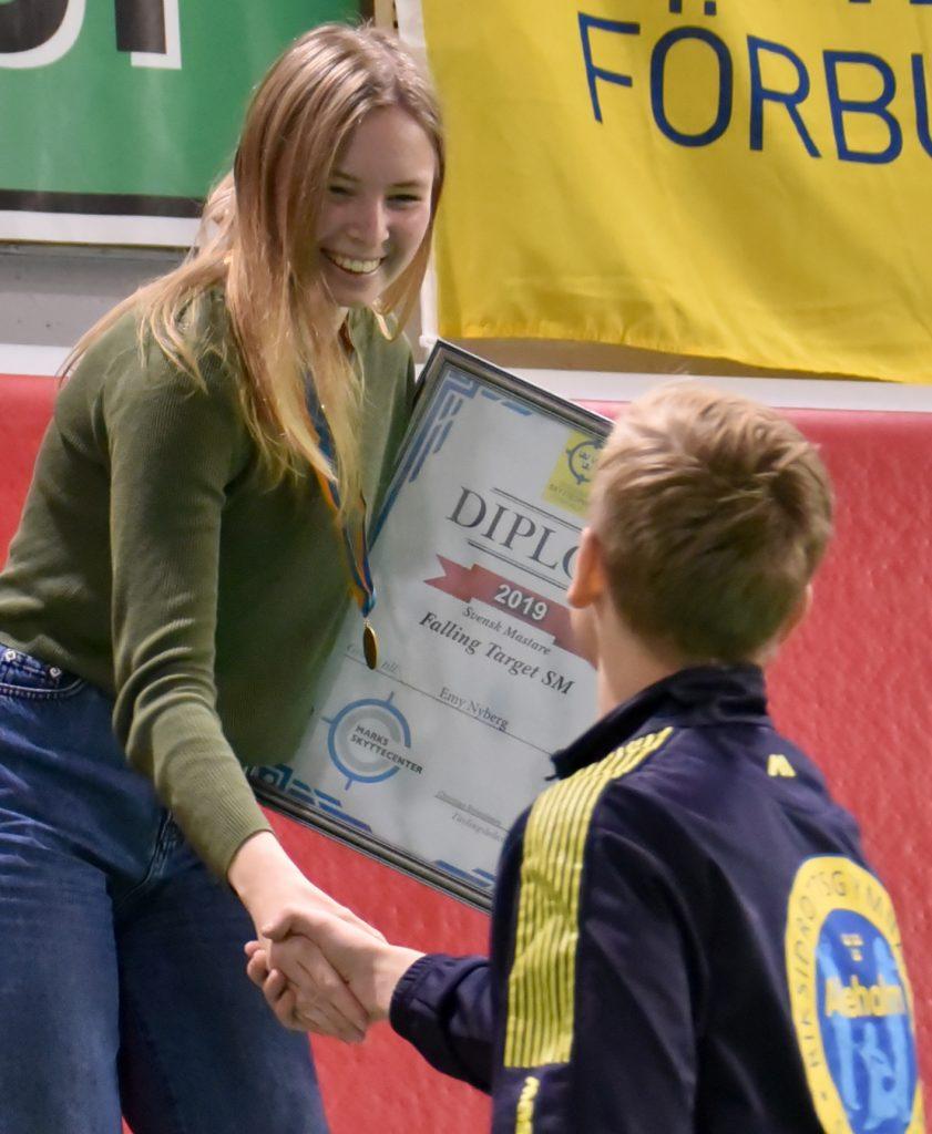 Emy Nyberg med guldmedalj och diplom, skakar hand med elev från skyttegymnasiet.