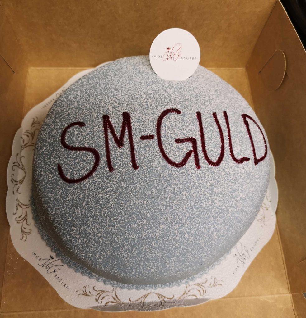 En blå prinsesstårta med texten SM-guld.