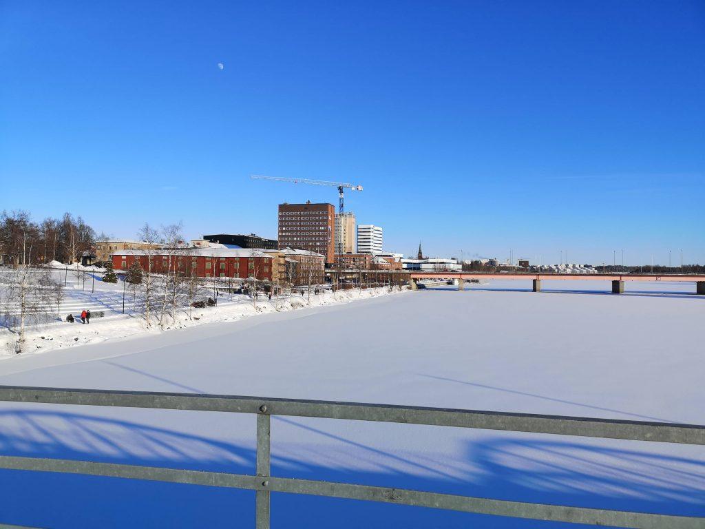 En bild på Umeå med snö och blå himmel
