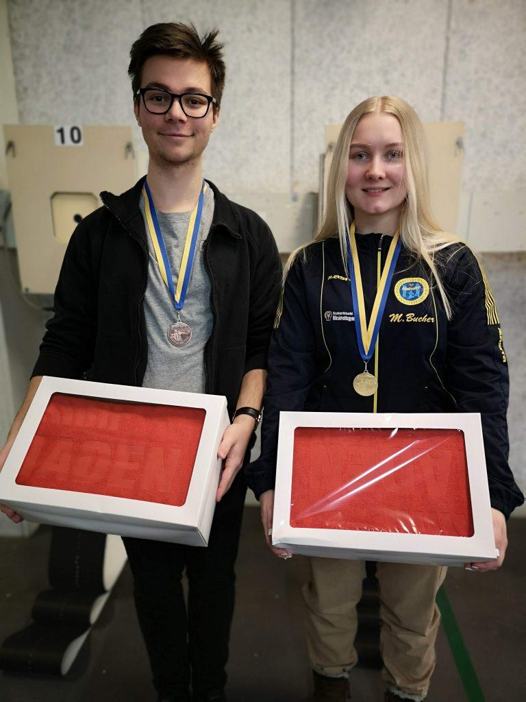 Alexander och Maja visar sina medaljer och handdukar.